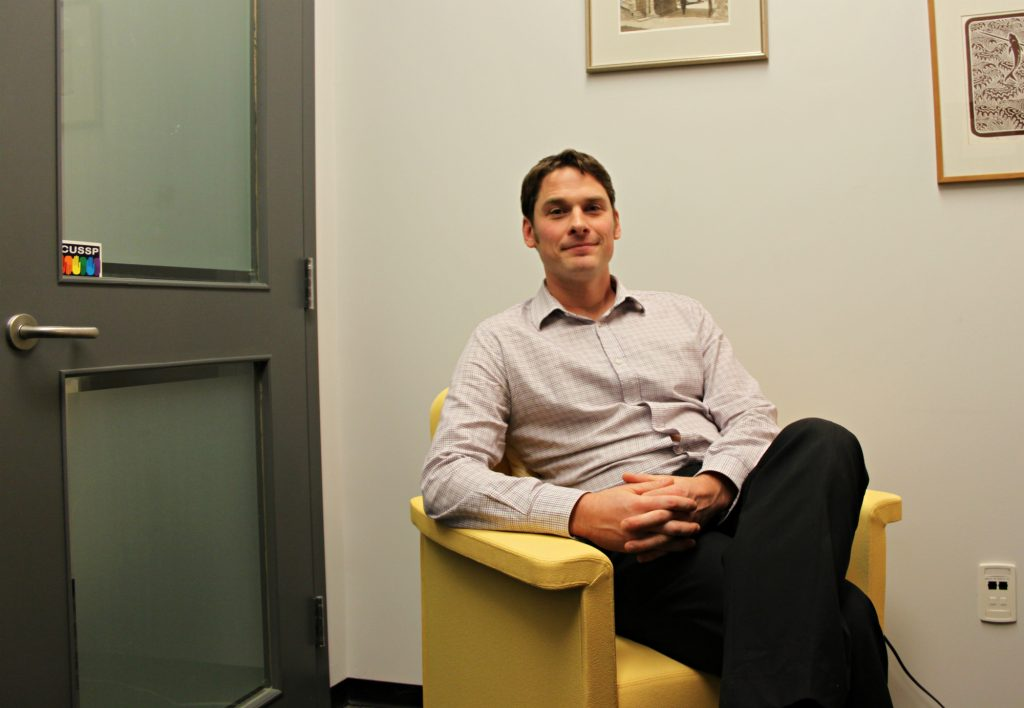 Nathaniel Jewitt, a counsellor for Carleton's Health and Counselling services helps students in residence who might be dealing with anxiety and depression. He's pictured here in his office. Photo by Olivia Bowden.